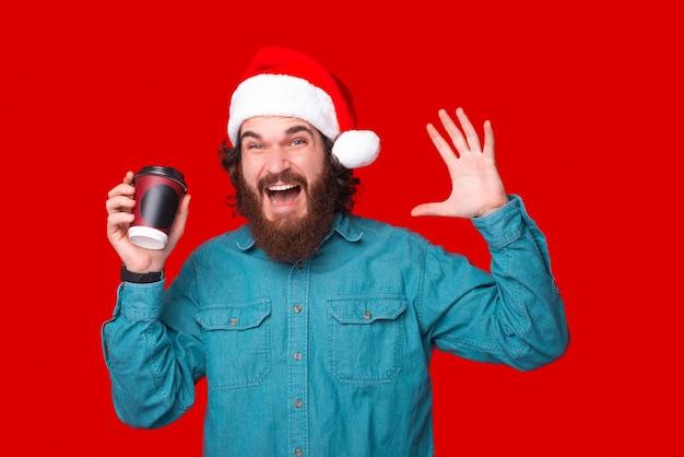 Was für ein guter kaffee. erstaunter junger mann mit bart trägt weihnachtsmann-hut und hält eine tasse kaffee zu g