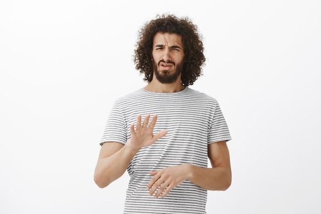 Was für eine schreckliche idee, nein. porträt eines unzufriedenen, angewiderten, gutaussehenden männlichen models mit bart und afro-frisur, zitternder handfläche oder ausreichender geste, stirnrunzeln vor abneigung