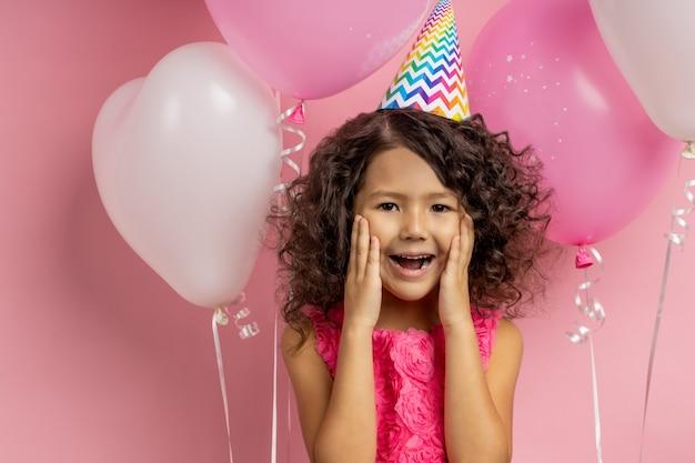 Was für eine überraschung. nettes überglückliches kaukasisches kleines mädchen im kleid, partyhut, stehend zwischen luftballons mit offenem mund, handflächen auf schecks haltend, lang erwartetes geschenk empfangend, posierend.