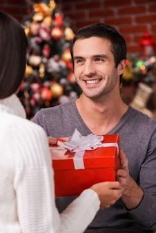 Was fuer eine ueberraschung! rückansicht eines jungen mannes, der seiner freundin eine rote geschenkbox mit weihnachtsbaum im hintergrund gibt