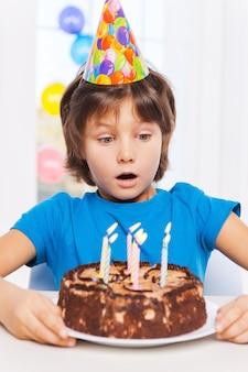Was fuer eine ueberraschung! überraschter kleiner junge, der den geburtstagskuchen betrachtet und sich darauf vorbereitet, die kerzen auszublasen