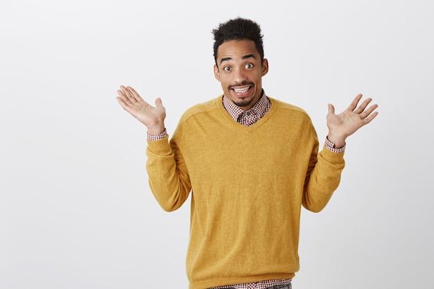 Was getan wurde, kann nicht geändert werden. porträt eines verwirrten, ahnungslosen, emotionalen, dunkelhäutigen mannes mit afro-frisur, der die handflächen zur kapitulation erhebt, achselzuckend und ahnungslos lächelt und keine ahnung von der grauen wand hat