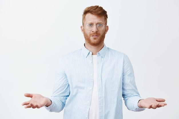 Was habe ich falsch gemacht. verwirrter düsterer gutaussehender rothaariger kerl mit bart in brille und hemd, der mit fragendem gesichtsausdruck steht und handflächen in ahnungsloser pose ausbreitet, ahnungslos und unsicher ist, was passiert ist
