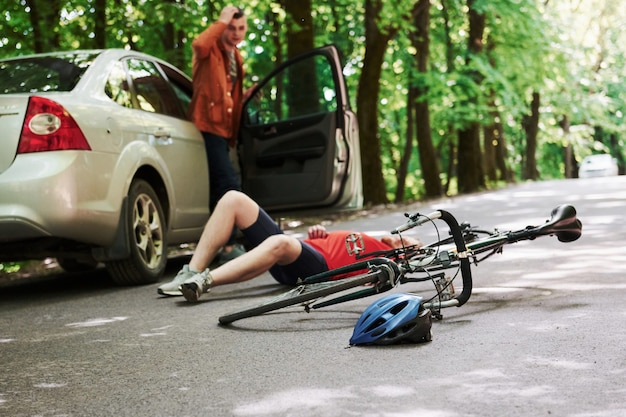 Was habe ich gemacht. opfer auf dem asphalt. fahrrad und silberfarbener autounfall auf der straße am wald während des tages