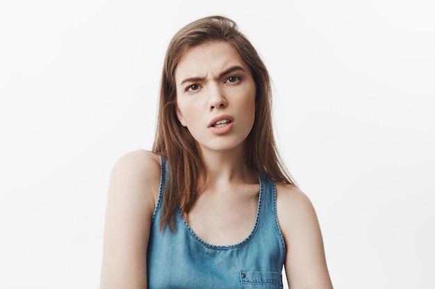 Was hast du gesagt? junges schönes dunkelhaariges studentenmädchen in blauem hemd mit gemeinem und aggressivem ausdruck, nachdem du beleidigende worte von einem beliebten mädchen an der universität gehört hast