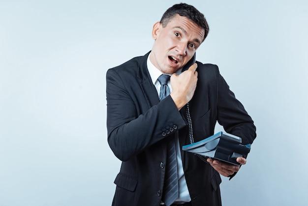 Was hast du gesagt. taille hoch aufnahme eines verwirrten männlichen arbeiters in einem schwarzen anzug, der ein bürotelefon hält und jemandem während eines telefongesprächs zuhört, wobei sein gesicht in die kamera verzieht.