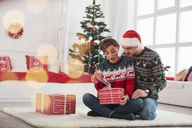 Was ist da drin. mann überraschen seine frau zu weihnachten im schönen zimmer mit weihnachtsschmuck