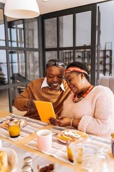 Was ist das. erfreuter positiver mann, der auf den tablettbildschirm zeigt, während er mit seiner frau sitzt