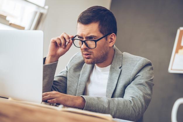 Was ist das? hübscher junger mann, der seinen laptop betrachtet und seine brille beim sitzen an seinem arbeitsplatz justiert