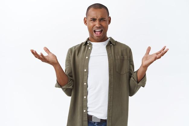 Was ist dein problem. porträt eines frustrierten und verärgerten afroamerikaners, der die hände seitlich ausbreitet und sich beschwert
