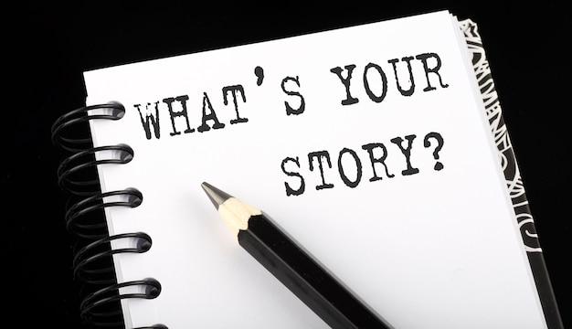 Was ist deine geschichte auf einem notizbuch mit einem schwarzen bleistift auf schwarzem hintergrund geschrieben