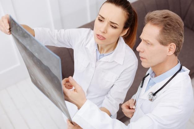Was ist deine meinung. bestimmte ausgezeichnete qualifizierte chirurgen, die den fortschritt der krankheit diskutieren, während sie die mrt-scans der patienten durchsehen und besorgt aussehen
