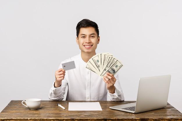 Was ist deine wahl. der hübsche erfreute und reiche, erfolgreiche männliche unternehmer, der großes bargeld, dollar und kreditkarte zeigt, das lächeln erfreut, rat halten geldeinzahlung, wählen seine bank