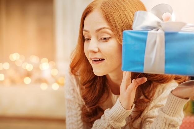 Was ist innen. aufgeregte frau kann es kaum erwarten, ihr weihnachtsgeschenk zu öffnen und zu erraten, was sie am weihnachtsmorgen bekommen hat.
