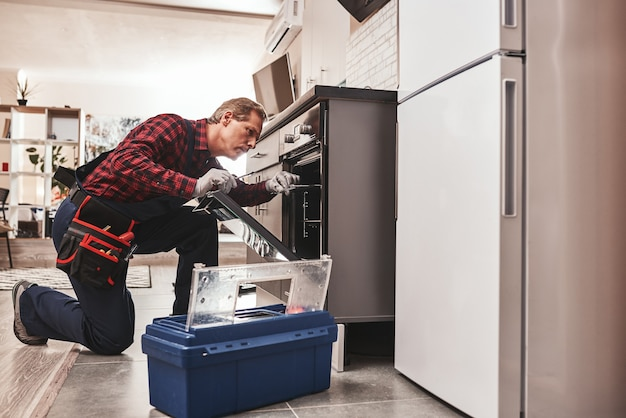 Was ist mit dem ofen in voller länge von einem handwerker, der den ofen untersucht?