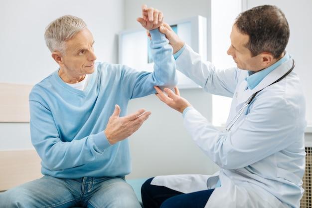 Was ist mit mir? besorgter ängstlicher alter mann, der seine hand hochhält und den arzt ansieht, während er sich sorgen um seine gesundheit macht