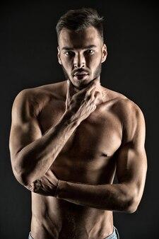 Was ist, wenn ich dir meine muskeln zeige. das nachdenkliche gesicht des mannes sieht attraktiven schwarzen hintergrund aus. athlet sexy muskulöser körper auf selbstbewusstem gesicht. mann muskulöser torso angespannte muskelvenen berühren das kinn beim denken.