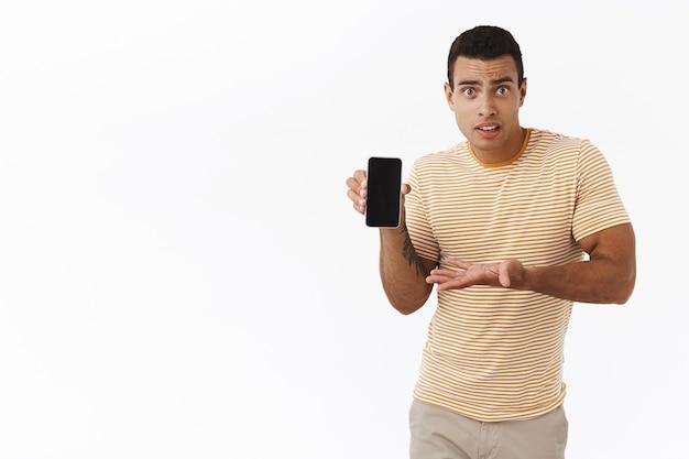 Was sollte ich tun. verwirrter und besorgter, gutaussehender mann zuckt mit den schultern und fragt einen freund, der sein profil auf dem smartphone zeigt
