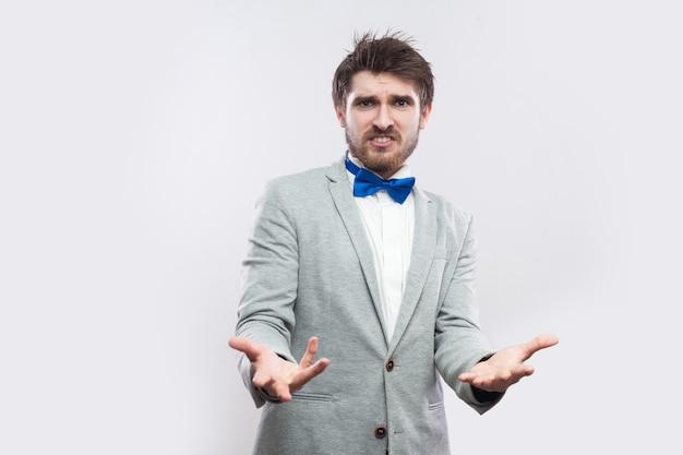Was willst du? porträt eines wütenden, gutaussehenden bärtigen mannes in lässigem grauem anzug, blauer fliege, erhobenen armen, blick in die kamera und nachfragen. indoor-studioaufnahme, isoliert auf hellgrauem hintergrund.