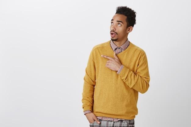 Was zum teufel ist das. innenaufnahme eines befragten neugierigen afrikanischen mannes mit afro-haarschnitt, der auf die obere linke ecke zeigt und schaut, interessantes ding sieht und es mit freunden bespricht