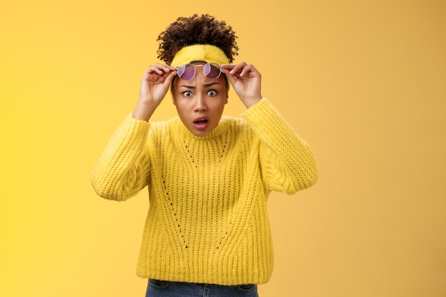 Was zum teufel. schockiert fassungslos verwirrt afroamerikanisches stilvolles modernes mädchen in pullover-stirnband-take-off-sonnenbrille weiten die augen überrascht sprachlos keuchender blick in frage gestellter ausflippen, gelber hintergrund.
