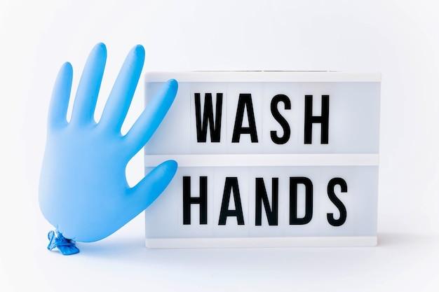 Wasch deine hände. text auf leuchtkastenanzeige mit blauem handschuhballon auf leuchttisch.