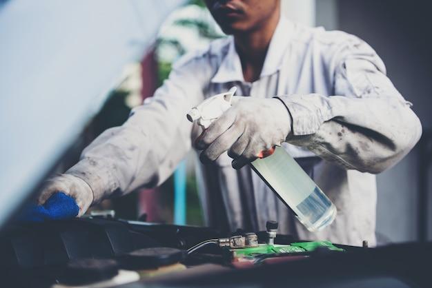 Waschanlagearbeitskraft, die eine weiße uniform steht einen schwamm trägt, um das auto in der waschanlagemitte, konzept für autopflegeindustrie zu säubern.