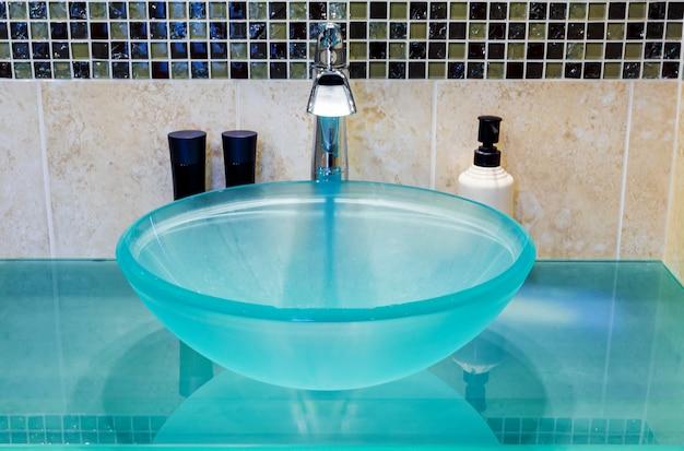 Waschbecken gemacht vom ausgeglichenen glas auf holztisch, weißer backsteinmauerhintergrund