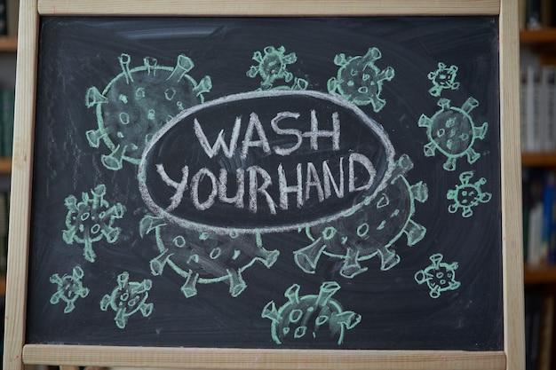 Wasche deine hand. ausbruchswarnung. geschriebene weiße kreide auf tafel im zusammenhang mit epidemischem coronavirus weltweit covid 19 pandemie text auf schwarzem hintergrund mit freiem speicherplatz. gezogene virusbakterien Premium Fotos