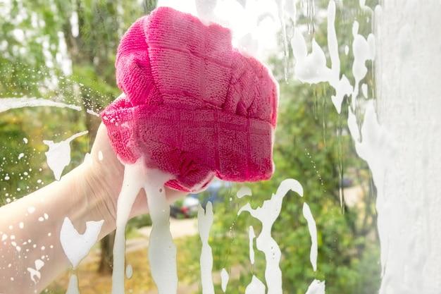 Waschen eines schmutzigen fensters auf einem grünen hintergrundbaum. service zum fensterputzen.
