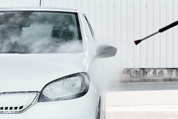 Waschen eines weißen elektroautos in hochdruckwasser bei manueller autowäsche. reinigungsservicekonzept