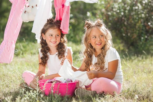 Waschen mit zwei kleinen mädchen. schwestern bei der hausarbeit