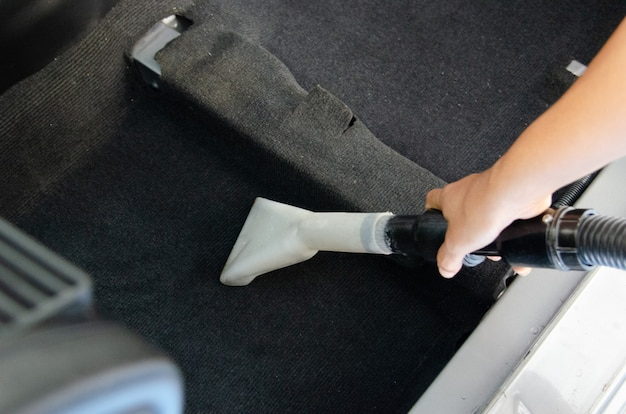 Waschen sie den autoteppich.detailliert auf das innere des modernen autos.staubsaugen und reinigen sie das innere des autos.