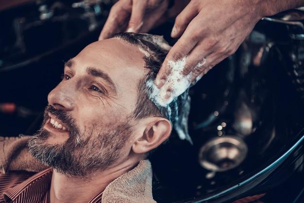 Waschen sie ihre haare, bevor sie einen kunden in einem friseurladen abschneiden.