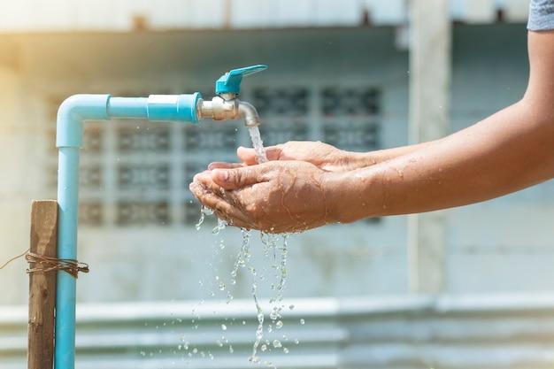 Waschen sie ihre hände mit sauberem wasser aus dem wasserhahn.