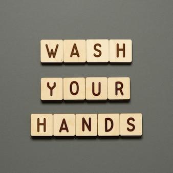 Waschen sie ihre hände - wörter aus holzklötzen mit buchstaben. draufsicht