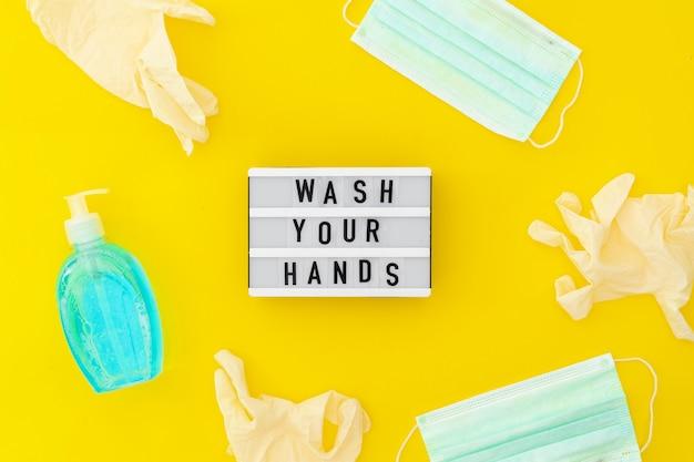 Waschen sie ihren handleuchtkasten mit einer medizinischen maske, einer leichten seife und medizinischen handschuhen. draufsicht auf gelbem hintergrund