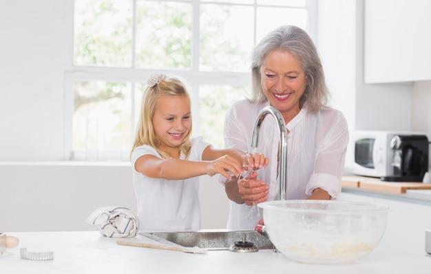 Waschende hände der großmutter und der enkelin