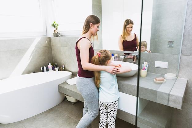 Waschende hände der jungen frau und des mädchens
