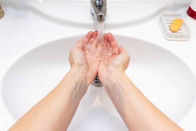 Waschende hände einer frau mit wasser in der badezimmerwanne