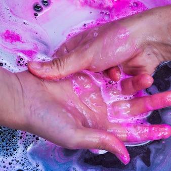 Waschende hände in der blauen flüssigkeit