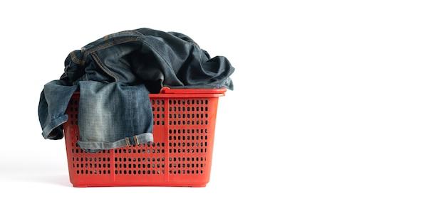 Waschender korb voll der kleidung und der verblaßten jeanshose lokalisiert auf weißem hintergrund mit beschneidungspfad