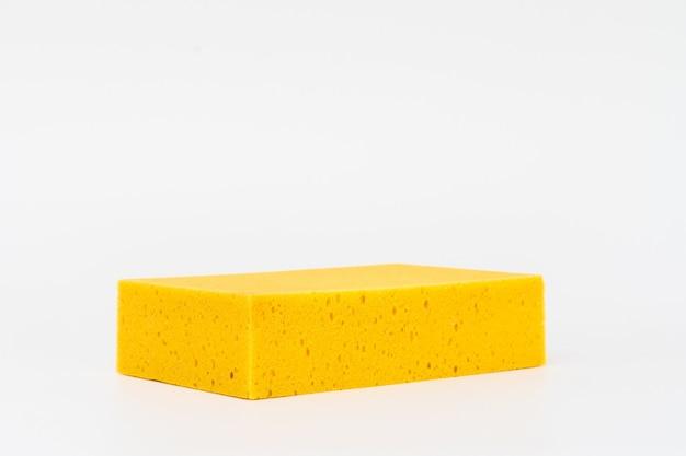 Waschender schwamm des gelben autos nah oben auf weißer szene.
