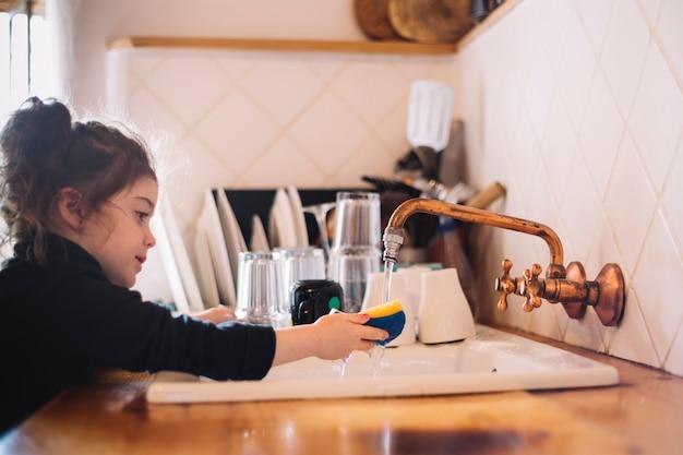 Waschender schwamm des netten mädchens in der küchenwanne