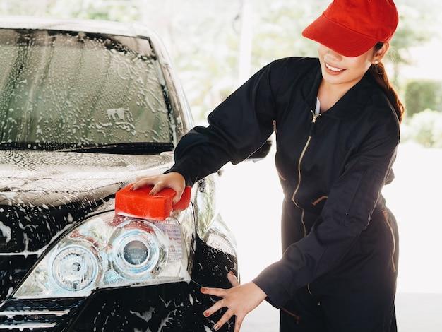 Waschendes auto der asiatinarbeitskraft an der garage