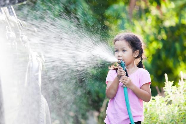 Waschendes auto des glücklichen asiatischen kindermädchenhilfs-elternteils auf dem wasser, das mit sonnenlicht spritzt