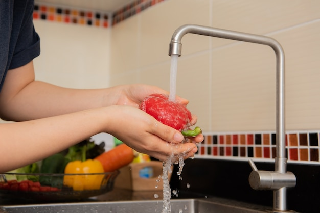 Waschendes gemüse der frau auf dem worktop nahe, zum in einen modernen kücheninnenraum zu sinken