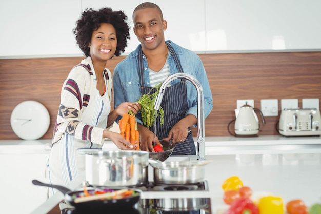 Waschendes gemüse des glücklichen paars in der küche