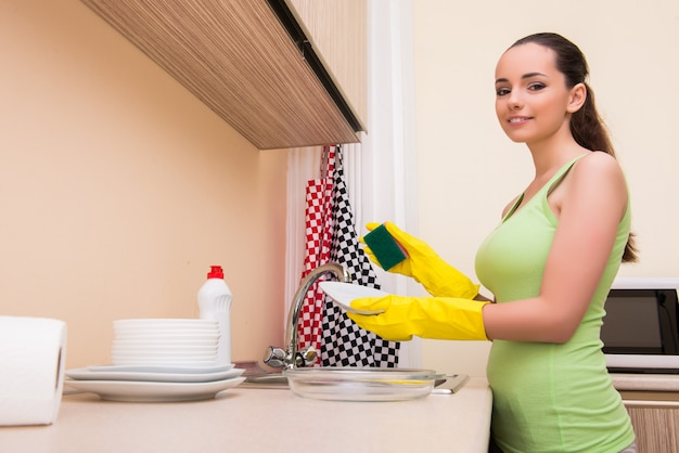 Waschendes geschirr der jungen frau frau in der küche