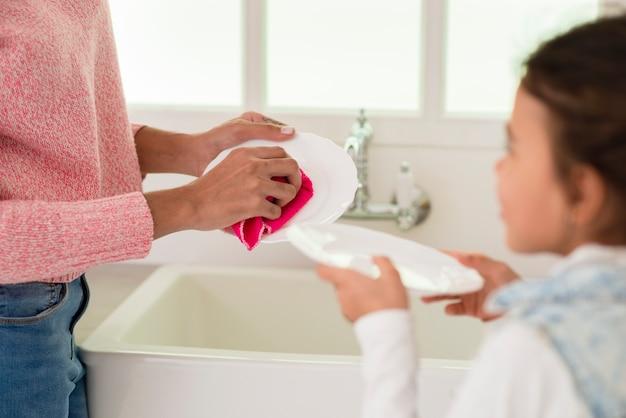 Waschendes geschirr der nahaufnahmemutter und -tochter